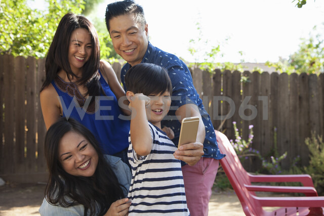 Family with boy posing for smartphone selfie in garden - ISF13244 - Corina Marie Howell/Westend61