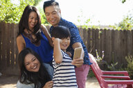 Family with boy posing for smartphone selfie in garden - ISF13244