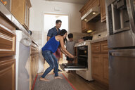 Boy and parents putting tray into kitchen oven - ISF13250