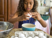Girl cracking eggs into bowl looking down - ISF13262