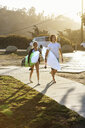 Couple carrying surfboards, walking towards beach - ISF13349