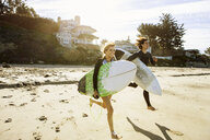Couple running towards sea, carrying surfboards - ISF13355