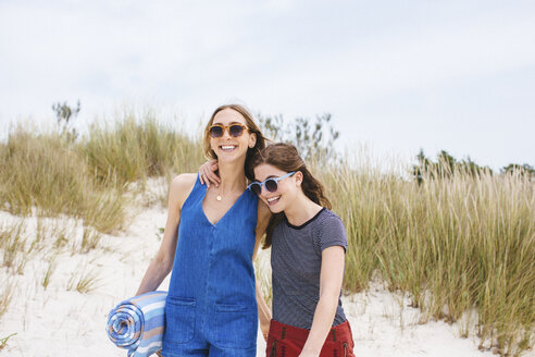 Two young female friends on sand dunes carrying picnic blanket - ISF13370