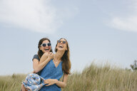 Two young female friends carrying picnic blanket laughing on dunes - ISF13376