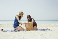 Two young female friends emptying picnic basket on beach - ISF13382