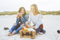 Two young female friends preparing picnic on beach - ISF13424