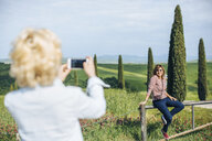 Two mature female friends taking smartphone photograph in landscape, Tuscany, Italy - ISF13466