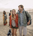 Group of friends walking along beach, young couple looking at smartphone - ISF13523