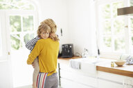Mother carrying son in kitchen - ISF13643