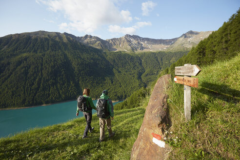 Rear view of young couple hiking at Vernagt reservoir, Val Senales, South Tyrol, Italy - ISF13679