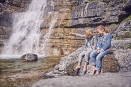 Brother and sister, sitting on rock, relaxing, beside waterfall - ISF13751