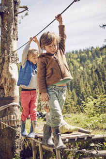 Two children walking across single rope bridge - ISF13754