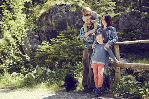 Portrait of family, in forest, standing by fence - ISF13760
