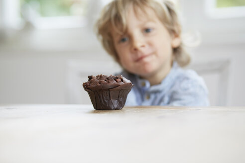 Young boy staring at chocolate muffin - ISF13766