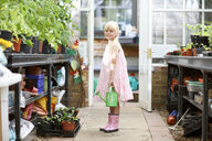 Portrait of pretty girl holding watering can in greenhouse - ISF13787