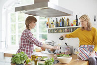 Women preparing meal in kitchen - ISF13814