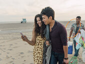 Group of friends walking along beach, young couple looking at smartphone - ISF13865