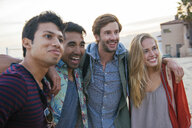 Group of friends standing together on beach, laughing - ISF13868