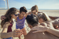 Group of friends in huddle on beach - ISF13883