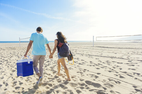 Young couple walking on beach, holding cool box, rear view - ISF13913