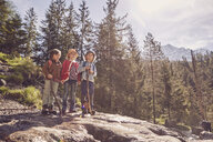 Three children standing on rock in forest - ISF13961