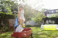 Girl in butterfly costume standing in toy wagon - ISF14009