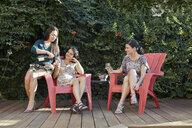 Three women drinking white wine on patio - ISF14030