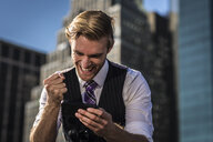 Young businessman in front of office clenching fist at smartphone, New York, USA - ISF14036