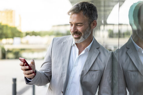 Portrait of smiling businessman leaning against glass facade looking at smartphone - AFVF00635