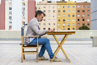 Businessman sitting on roof terrace working on laptop - AFVF00644