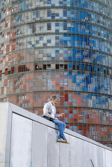 Spain, Barcelona, businessman sitting on wall using cell phone - AFVF00650