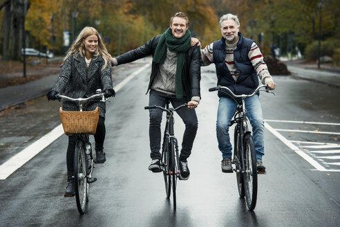 Friends cycling on street - CUF33166