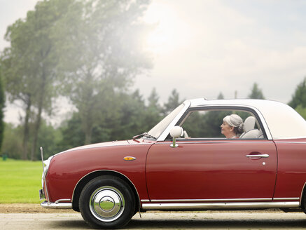 Senior woman driving along in red convertible - CUF33232