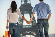Young couple strolling in front of  Eiffel Tower, Paris, France - CUF33241