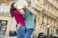 Young couple hiding behind map, Paris, France - CUF33244
