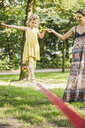 Young girl with mother walking slackline in park - CUF33250