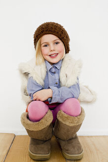 Studio portrait of young girl in oversize boots - CUF33283