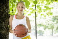 Portrait of young female basketball player in park - CUF33355