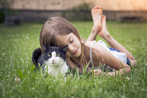 Little girl cuddling with cat on a meadow - LVF07125