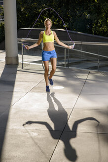 Young female athlete skipping in urban sunlight - CUF33489