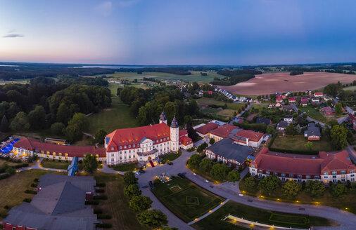Germany, Mecklenburg-Western Pomerania, Mecklenburg Lake District, Goehren-Lebbin, Aerial view of Castle Hotel Fleesensee in the evening - AMF05761