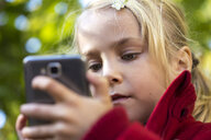 Portrait of little girl using smartphone - JFEF00886