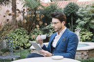 Elegant businessman using tablet in a garden cafe - ALBF00537