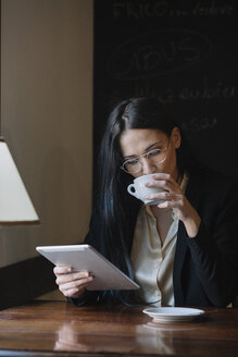 Young businesswoman drinking coffee and using tablet in a cafe - ALBF00555