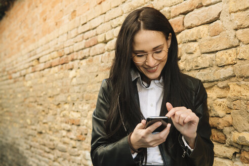 Smiling young woman using cell phone at brick wall - ALBF00570