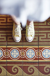 Woman wearing yellow sneakers standing on mosaic floor, partial view - ABIF00639