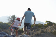 Father and daughter walking in hills hand in hand, Almeria, Andalusia, Spain - CUF33689