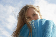 Portrait of girl wrapped in towel at breezy coast - CUF33716