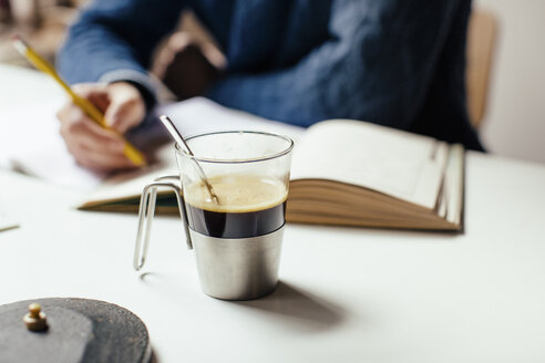 Coffee cup on table, man writing in background - CUF33746