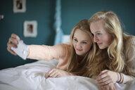 Two teenage girls taking selfie in bedroom - CUF33779